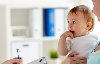 infant held by his mom while a doctor takes notes